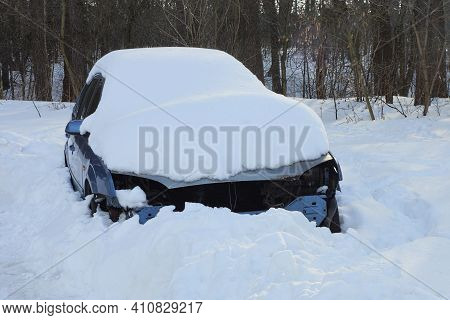 One Blue Wrecked Car After An Accident In A Snowdrift Of White Snow On A Ziney Street Against A Back