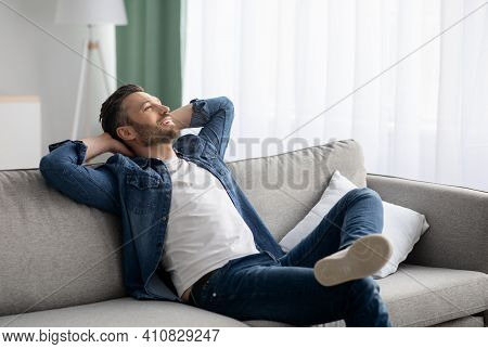 Weekend At Home. Relaxed Middle-aged Bearded Man In Casual Resting At Home, Holding Hands Behind Hea