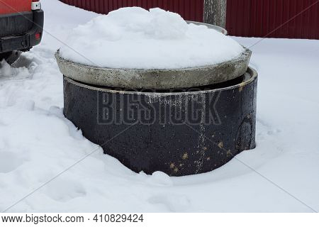 One Black Concrete Circle Covered With A Gray Lid Stands In A Snowdrift Of White Snow On A Winter St