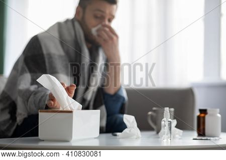 Sick Man Covered In Blanket Sitting On Couch And Sneezing Runny Nose, Taking Napkins, Selective Focu