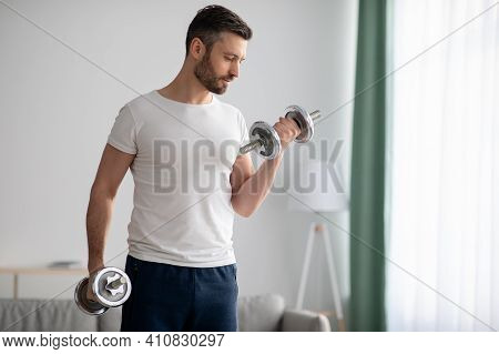 Closeup Of Handsome Middle-aged Man Doing Dumbbell Workout At Home, Working On Arms Strength, Lookin
