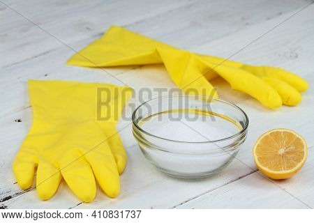 Crystalline Citric Acid In A Bowl, Good For Cleaning.  Rubber Gloves And Lemon Cut In Half On The Wh