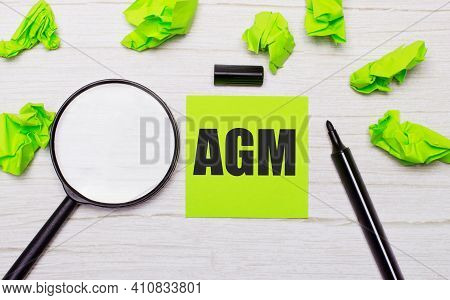 The Words Agm Annual General Meeting Written On A Green Sticky Note Next To A Magnifying Glass And A