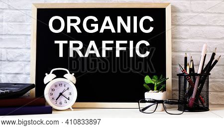 The Words Organic Traffic Is Written On The Chalkboard Next To The White Alarm Clock, Glasses, Potte