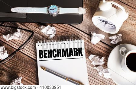 There Is A Cup Of Coffee On A Wooden Table, A Clock, Glasses And A Notebook With The Word Benchmark.