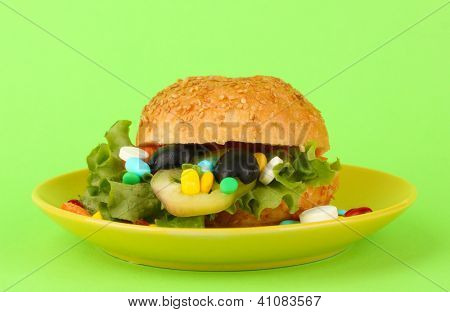 Conceptual image for nutritional care:assorted vitamins and nutritional supplements in bun.On color background