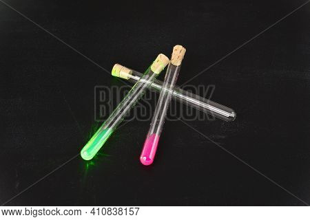 Laboratory Glass Flasks Filled With Luminous Liquid On Dark Background.