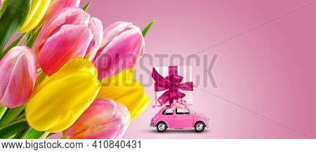 Pink Retro Car With Gift Box On A Roof With Tulip Flowers On Pink Background. Greeting Card, Banner