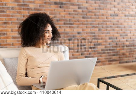 Young African American Female Freelancer With Afro Hairstyle Sitting On The Couch And Working On The