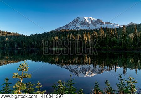 Mount Rainier Shows Off Its Reflection In A Mirrored Lake During The Early Hours Of The Morning.