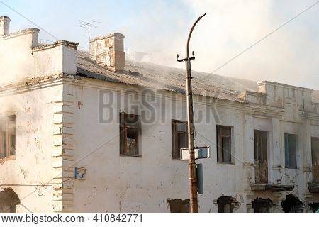 The Front Of An Abandoned House, Smoke Comes From The Windows Of The House. An Abandoned House In A