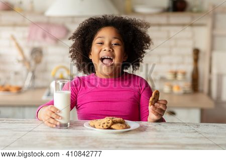 Cheerful Little Black Girl Sitting At Table Enjoying Milk And Cookies, Cute African American Child H