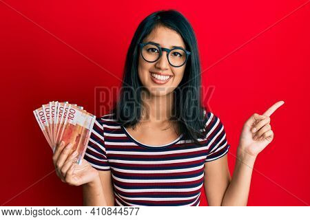 Beautiful asian young woman holding 100 norwegian krone banknotes smiling happy pointing with hand and finger to the side