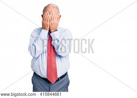 Senior handsome grey-haired man wearing elegant tie and shirt with sad expression covering face with hands while crying. depression concept.