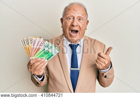 Senior caucasian man holding norwegian krone banknotes pointing thumb up to the side smiling happy with open mouth