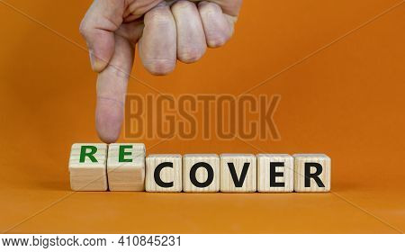 Time To Recover Symbol. Businessman Turns Wooden Cubes And Changes The Word 'cover' To 'recover'. Be