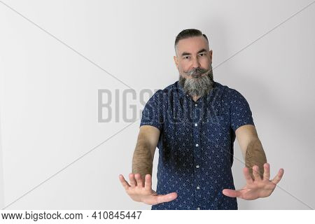 40-45 Year-old Caucasian Hipster With A Big Gray Beard, With A Serious Face And Hands Forward In A C