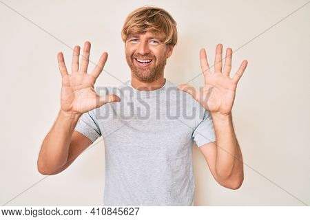Young blond man wearing casual clothes showing and pointing up with fingers number ten while smiling confident and happy.