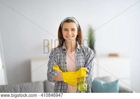 Joyful Young Housemaid In Rubber Gloves Holding Detergent And Smiling At Camera At Home. Lovely Mill