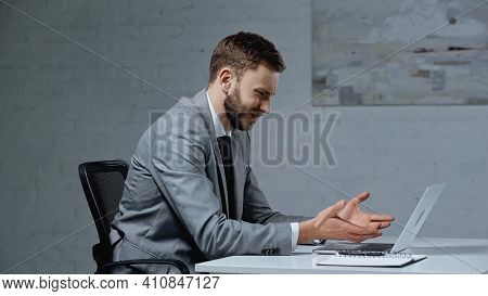 Displeased Young Businessman Gesturing While Looking At Laptop