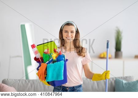 Cheerful Millennial Housewife Holding Bucket Full Of Cleaning Supplies At Modern Apartment. Portrait