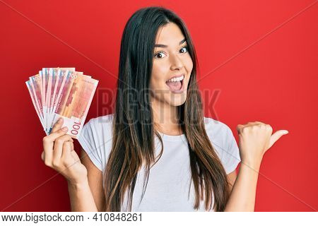 Young brunette woman holding 100 norwegian krone banknotes pointing thumb up to the side smiling happy with open mouth