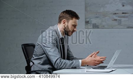 Displeased And Bearded Businessman Gesturing While Looking At Laptop