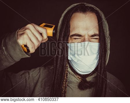 Miserable Man Posing With Thermometer Gun Over Dark Background