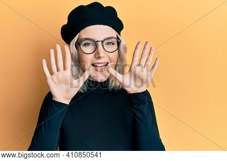Young blonde girl wearing french look with beret showing and pointing up with fingers number ten while smiling confident and happy.