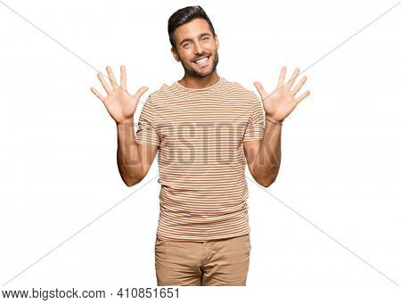 Handsome hispanic man wearing casual clothes showing and pointing up with fingers number ten while smiling confident and happy.