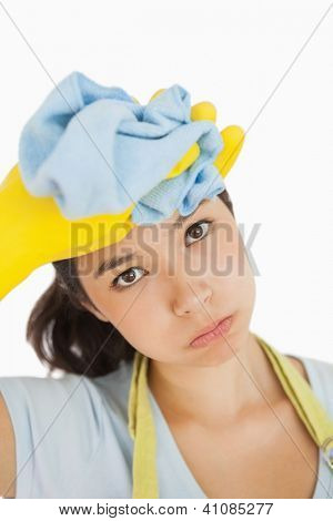 Woman wiping the sweat off her head wearing rubber gloves and holding rag