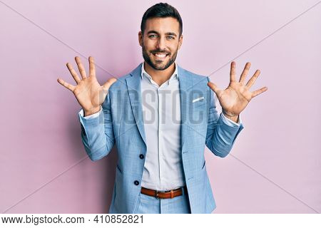Young hispanic businessman wearing business jacket showing and pointing up with fingers number ten while smiling confident and happy.
