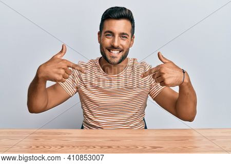 Handsome hispanic man wearing casual clothes sitting on the table looking confident with smile on face, pointing oneself with fingers proud and happy.