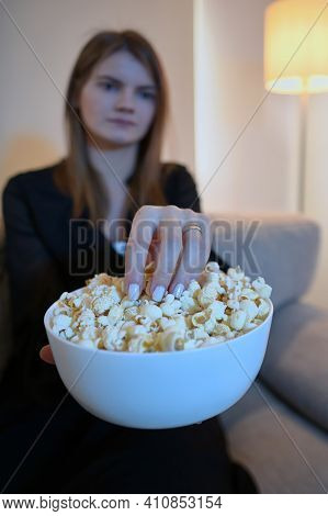 Young Woman Eating Popcorn On Sofa, Close Up