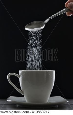 Tea Cup Or Coffee And Pouring Sugar Spoon On Black Background