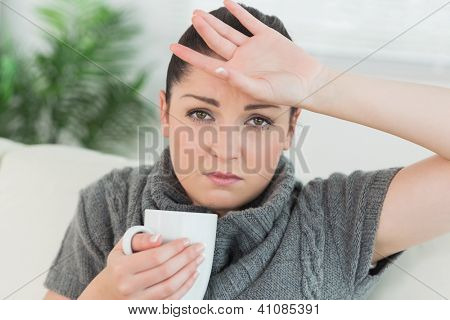 Young woman sitting on the couch in a living room while holding a cup and feeling ill