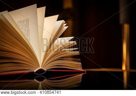 Close Up Of An Open Book Against Black