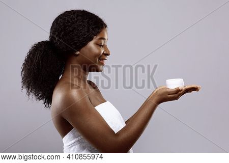 Attractive Black Female Wrapped In Towel After Bath Holding White Jar With Moisturising Face Cream I