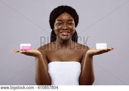Beauty Choice. Attractive Black Lady Wrapped In Towel Holding Two Jars With Moisturising Creams On H