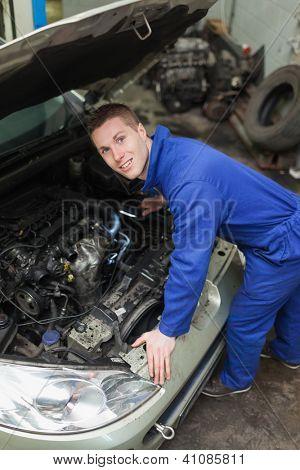 Portrait of male mechanic examining car engine