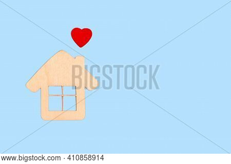Wooden House And A Red Heart. A Symbol Of Happiness In The Family, Warmth Of A Sweet Home, Love And