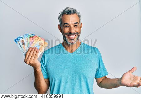 Middle age grey-haired man holding swiss franc banknotes celebrating achievement with happy smile and winner expression with raised hand