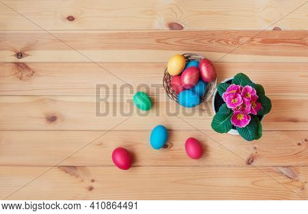 Colorful Easter Eggs In Wicker Basket  And Primula Flower On Wooden Table. Top View With Copy Space.