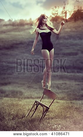 beautiful girl balances on back of chair outdoors. Artwork poster