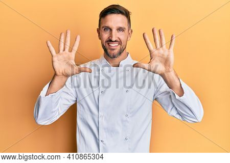 Handsome man with beard wearing professional cook uniform showing and pointing up with fingers number ten while smiling confident and happy.