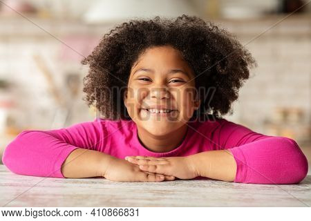 Happy Child. Closeup Portrait Of Cheerful Cute Little Black Girl Sitting At Table In Kitchen, Laughi