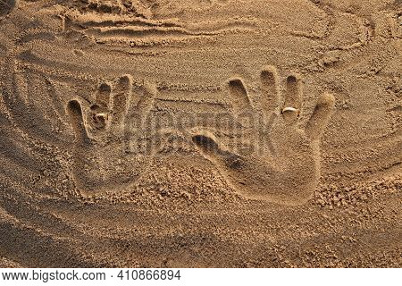 Wedding Rings In The Sand On The Footprints Of A Newly Married Couple.