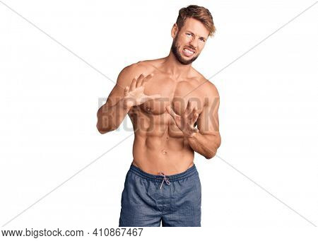 Young caucasian man standing shirtless disgusted expression, displeased and fearful doing disgust face because aversion reaction. with hands raised
