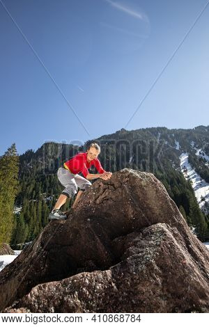 Young female climber putting climbing shoes on before climbing on a boulder outdoors, in Swiss Alps