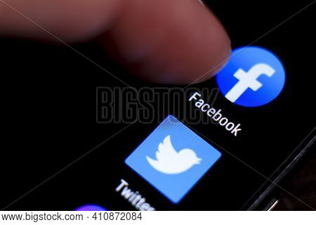 Madrid, Spain- March 3, 2021: Finger Pressing Facebook Icon On Black Mobile Phone Screen. Twitter Ic